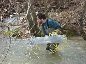 Figure 5. Placing a passive chemical sampler in the river.