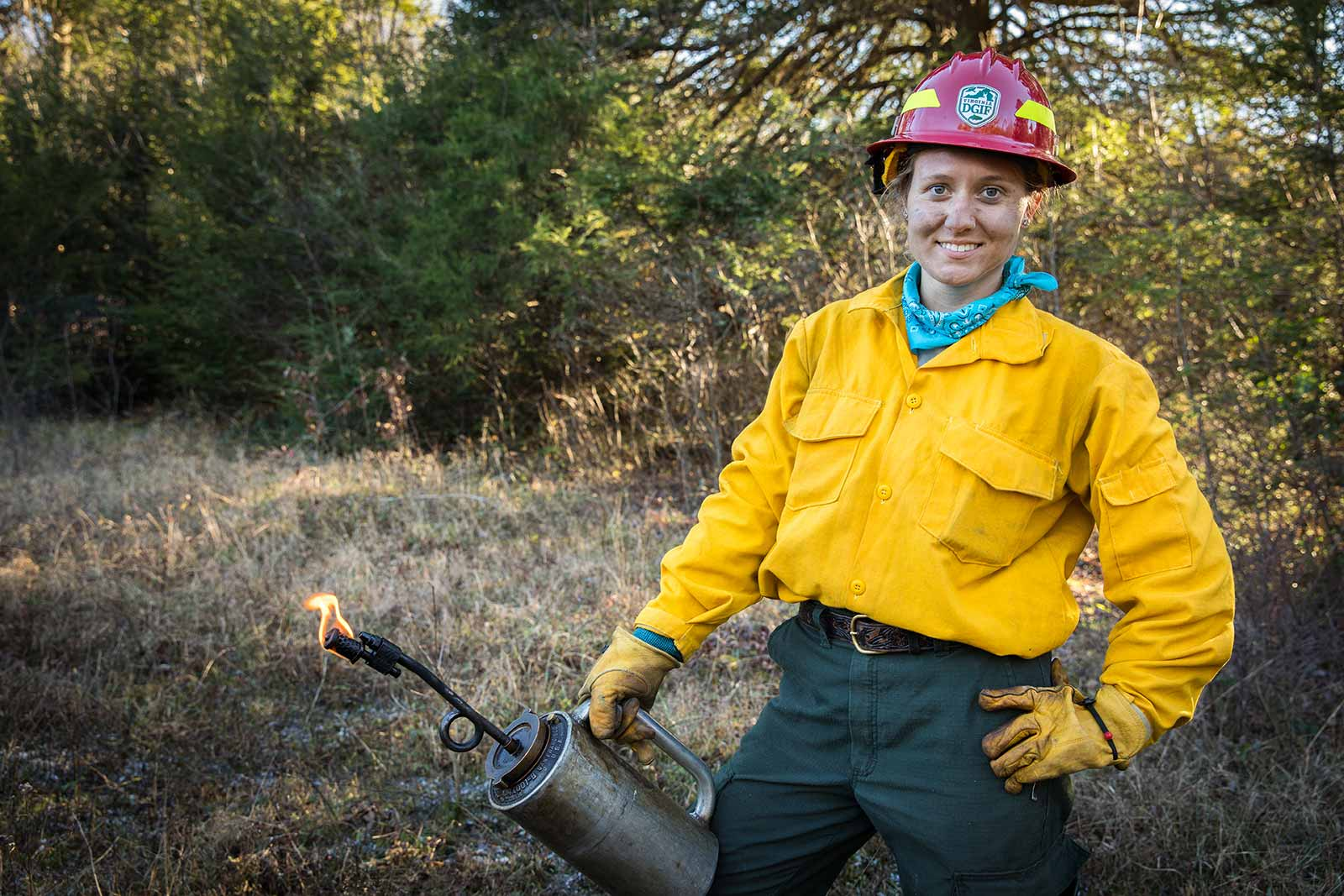 A fire crew member poses with a drip torch.